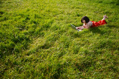 Relaxing work in nature. A young woman lying on the grass using a laptop computer Royalty Free Stock Images