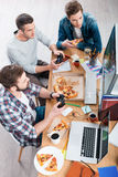 Relaxing after work. Top view of three young men playing computer games and eating pizza while sitting at the desk Stock Images