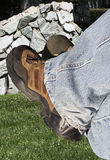 Relaxing worker. Legs with work boots relaxing in a park royalty free stock photo