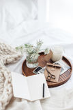 Relaxing or working at home concept. Wooden tray with paper notebook, old photos, candle and spring flowers on white bedding. Relaxing, or working, or writing Stock Photos