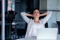 Relaxing at working place. Attractive young woman holding hands behind head and keeping eyes closed while sitting at her. Working place stock photography