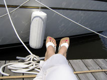 Relaxing at the Yacht Club. Close-up on woman's feet with pink nails with the white boat and ropes on the background Royalty Free Stock Photo