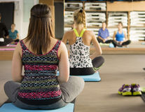 Relaxing yoga class. Group of young women meditating on yoga class stock photos