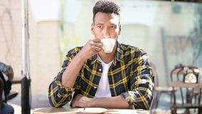 Relaxing Young African Man Drinking Coffee, Outdoor Cafe stock footage