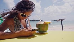 Relaxing young brunette woman wearing sunglasses using cellphone and drinking a cocktail from a coconut in the beach. 1920x1080 stock video