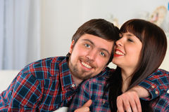Relaxing young couple sitting at couch Stock Photo