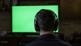 Relaxing young man with headphones playing video game in front of chroma key green screen tv monitor -. Relaxing young man with headphones playing video game in stock footage