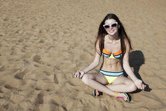 Relaxing young woman on the beach in a Lotus pose. Smiling attractive girl sit on the sand beach Stock Photo