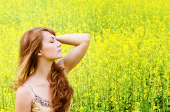 Relaxing young woman at canola field Stock Photo