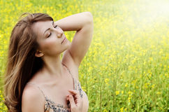 Relaxing young woman at canola field Royalty Free Stock Image