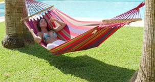 Relaxing young woman in colorful hammock stock video footage