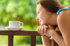 Young woman drinking cofee in a garden. Outdoors p. Ortrait Stock Photos