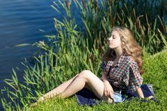 Relaxing young woman is sitting on the grass on the riverside. Royalty Free Stock Photos