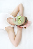 Relaxing young woman wearing green facial mask and cucumber slices on her eyes. Stock Photography