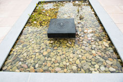 Relaxing zen fountain with pebbles and grass Stock Images