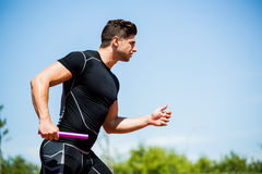 Relay athlete running with baton. Determined relay athlete running with baton running track royalty free stock photos