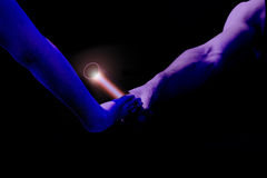 Relay race handing over blue shine. Male relay runner hands over the red baton to female runner. Blue filtered version royalty free stock photos