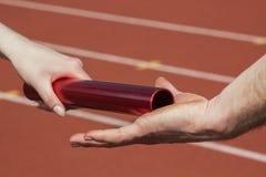 Relay race handing over. Female athlete hands over the relay race bar to a male athlete royalty free stock image