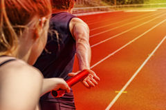 Relay race handing over female male. Relay race handing over from women to man royalty free stock photos