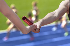 Relay race handing over. Male relay runner hands over the red baton to female runner royalty free stock photography