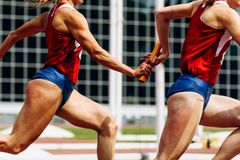 Relay race passing of baton. Women team runners royalty free stock photo