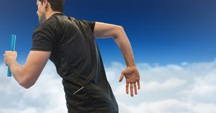 Relay runner against clouds and blue sky. Digital composite of Relay runner against clouds and blue sky stock photography
