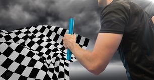 Relay runner mid section and flare against stormy sky and checkered flag. Digital composite of Relay runner mid section and flare against stormy sky and Stock Photo