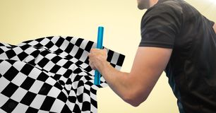Relay runner mid section and flare against yellow background and checkered flag. Digital composite of Relay runner mid section and flare against yellow Royalty Free Stock Image