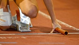 Relay runner in the starting blocks. At an indoor track and field event Royalty Free Stock Photography