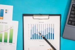 Relazione di attività con il computer portatile, calcolatore sul blu Immagini Stock