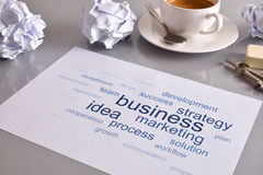 Relevant business words on sheet business concept message on des. Concept business with relevant business words on white  sheet on gray office table with Stock Photography