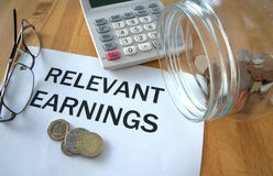 Relevant earnings. With coins on paper and in pot and calculator behind Royalty Free Stock Photo