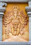 Relevo alaranjado do deus do elefante gravado na parede imagem de stock