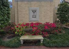 Relevo de pedra de uma pomba atrás de um banco e de uma conversão de flores vermelhas em Cristo o rei Catholic Church em Dallas,  fotografia de stock royalty free