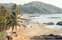 relexing和游泳在美丽的海洋海滩的人们在Vagator村庄附近 免版税库存照片
