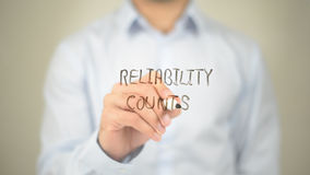 Reliability Counts, Man Writing on Transparent Screen stock images