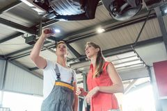 Reliable auto mechanic checking the car of a woman in a modern a. Low-angle view of a reliable auto mechanic, holding a flashlight while checking the parts of royalty free stock photos