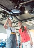 Reliable auto mechanic checking the car of a woman in a modern repair shop. Low-angle view of a reliable auto mechanic holding a flashlight, while checking the royalty free stock photos