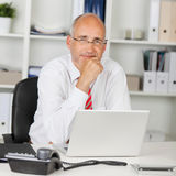 Reliable businessman with hand on chin Stock Image