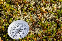Reliable compass on moss in tundra. Concept for travelling and active lifestyle