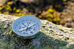Reliable compass on the stone in tundra. Concept for travelling and active lifestyle royalty free stock photography