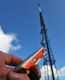 Reliable connection. Dialing a phonenumber on a cellphone under a telecommunication pole stock images
