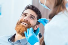 Reliable dentist using sterile instruments while cleaning the te. Side view of a reliable female dentist, using sterile instruments and blue surgical gloves stock photography