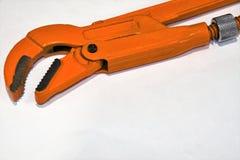 Orange Swedish pipe wrench close-up in isolation. royalty free stock image