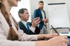 Reliable expert conducting a SWOT analysis during board of directors. Reliable expert wearing formal business suit while conducting a SWOT analysis during board Royalty Free Stock Image
