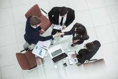 Reliable handshake business partners after the discussion of the financial contract in the office. Top view - reliable handshake business partners after the Royalty Free Stock Image