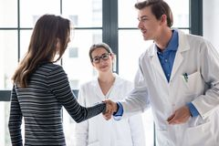 Reliable physician and female patient shaking hands before consultation. Young dedicated reliable physician and female patient shaking hands before consultation royalty free stock photo