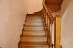 Oak staircase in the interior of the cottage`s living space. Reliable steps and high-quality perimeter fencing, from balusters and handrails. Upgrade to the stock photos