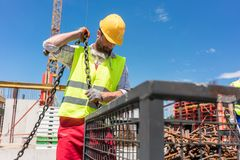 Reliable worker checking the safety latch of a hook. Reliable young worker checking the safety latch of a hook before lifting heavy weight with the crane on the stock images