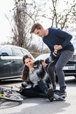 Reliable young man helping an injured woman while waiting for the ambulance stock image